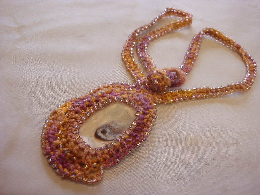 Looping necklace with shell center.