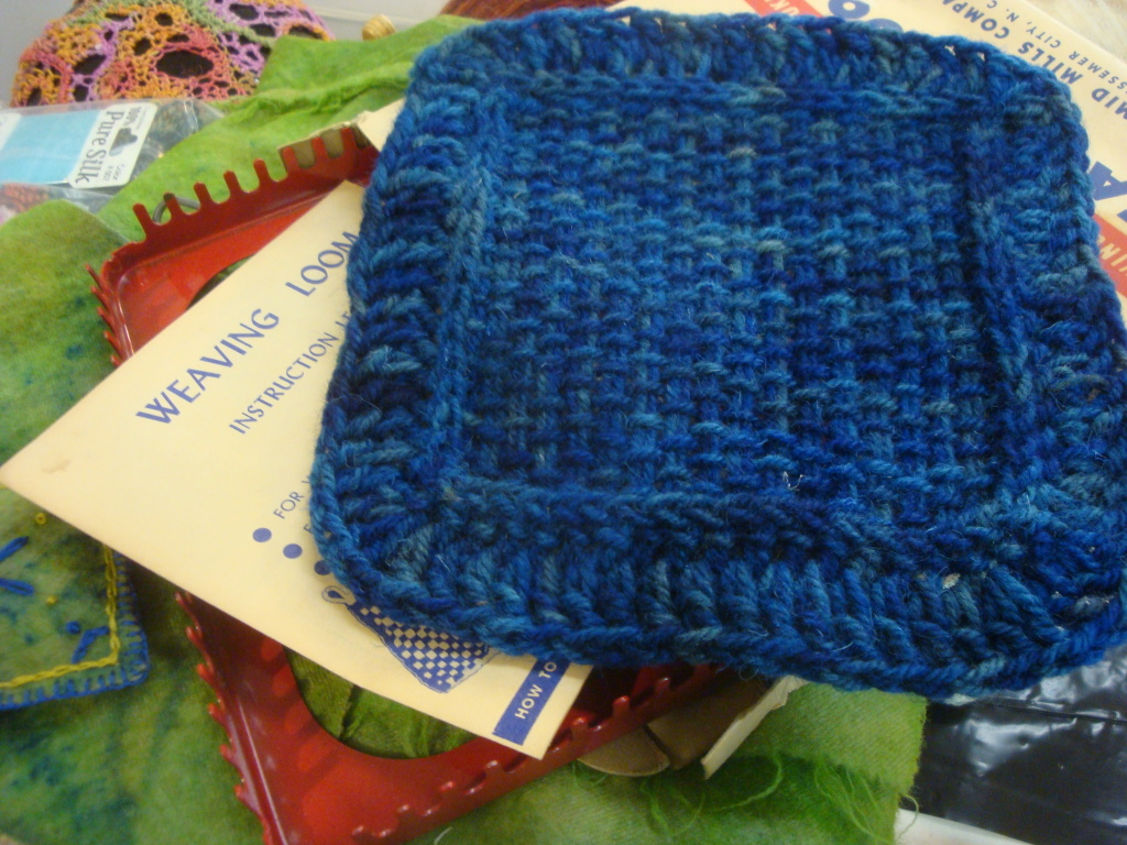 Table mat woven on a potholder loom using overdyed recycled wool yarn.