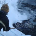 Rural artist Donna Kallner positioning looping installation in water.